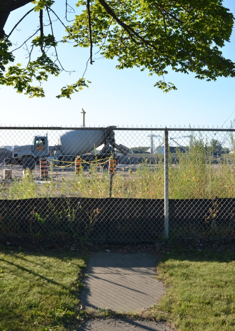 a path leads to a fence, construction site behind the fence, including a cement truck