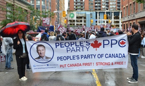 large white banner for the Peoples Party of Canada, in front of a protest on Church street