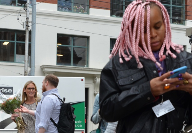 a young black woman with pink dreadlocks and a lot of rings on her fingers is on her phone as she passes by, in the background is a couple standing on the sidewalk having a conversation, the woman is holding a bouquet of flowers