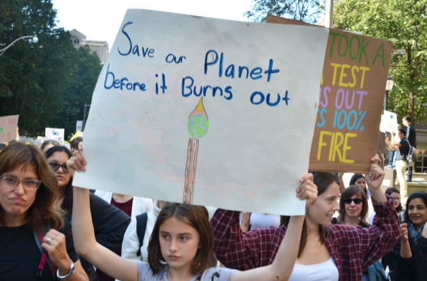 people at Toronto climate strike, walking along Wellesley street with signs, girl holds sign that says save our planet before it burns out