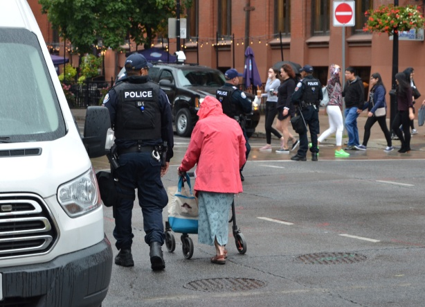 a police man escorts an older woman in a pink jacket who is using a walker, across an intersection
