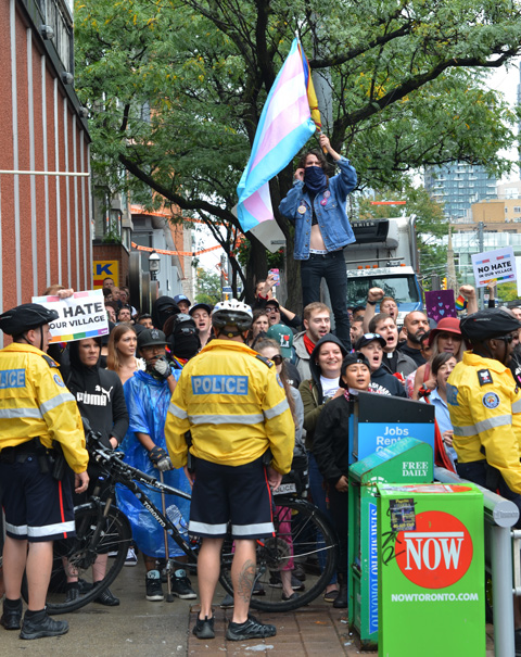 a person stands above a crowd holding a trans flag while police hold the crowd back
