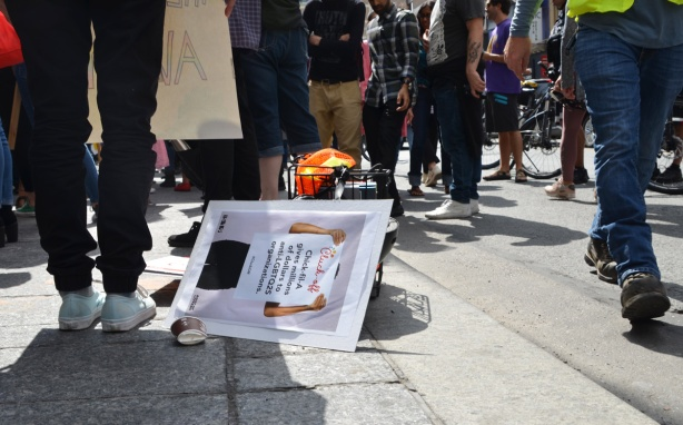 a protest sign lies on the sidewalk as people pass by