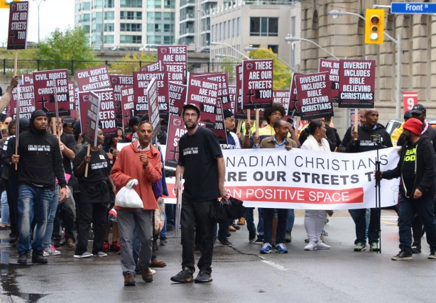 two men walk in front of a banner that says Canadian Christians share our streets, walking up yonge street at front street, other protesters are behind the banner.