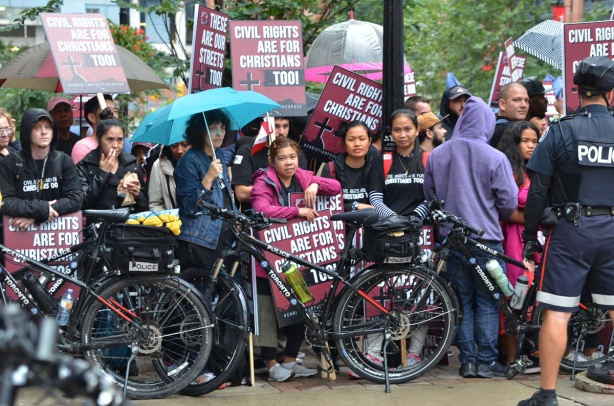 Christian protesters behind a line of police bikes