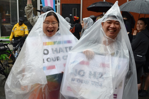 a couple wearing clear rain ponchos, laughing, holding signs under the ponchos that say No hate in our city