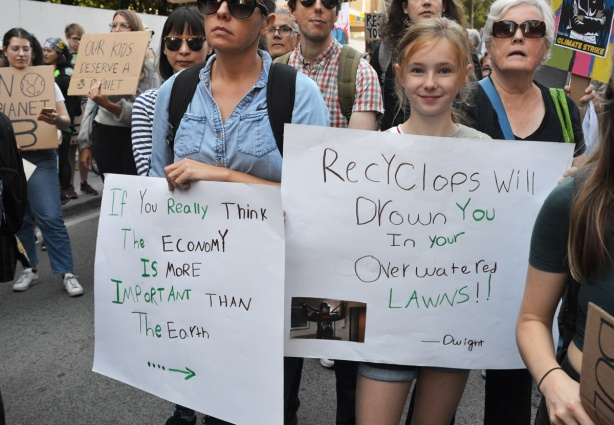 people at Toronto climate strike, walking along Wellesley street with signs, two people with signs, woman's sign says If you really think the economy is more important than the earth and has arrow pointing to girls' sign whose sign says Recyclops will drown in you overwatered lawns