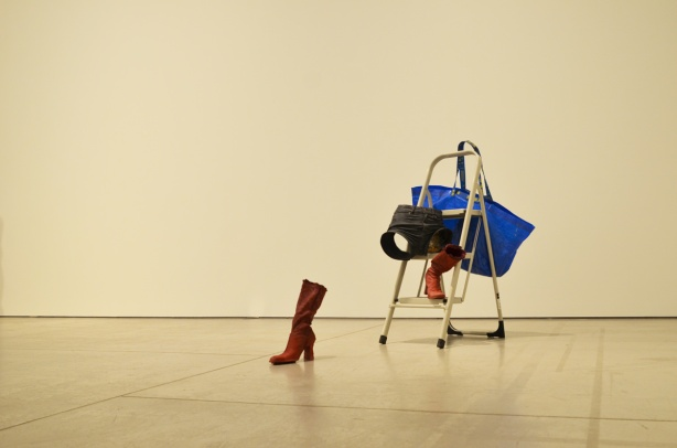 artwork by Valerie Blass at the Art Gallery of Ontario, one red boot, a pair of denim shorts and a blue ikea bag on a step stool