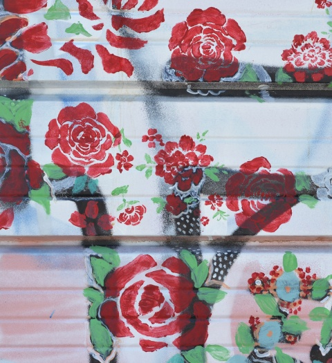 red rose stencil street art on a garage door