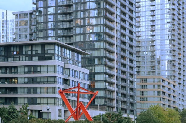 red sculpture in front of condo buildings