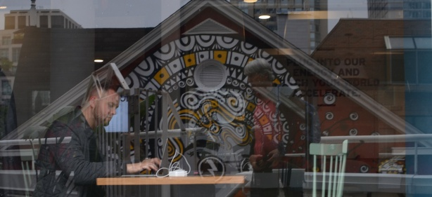 man working at a table, with reflections of a mural in the window, looking through the window
