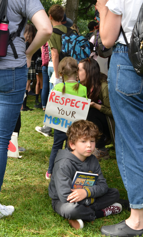 at the climate strike rally at Queens Park on a sunny morning in September, a young boy sits on the grass between two women. Behind him is girl with a sign on her back that says Respect your Mother