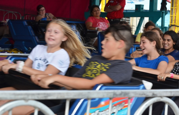 kids and other people on ride at Canadian National Exhibition that goes around in circles, fast, girl's long hair is flying out behind her