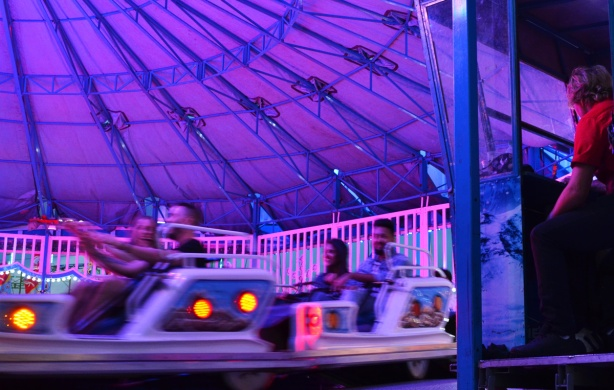 purple colour of the lights at a ride at the ex, man in red is at the controls, people with arms in air as they go around in circles