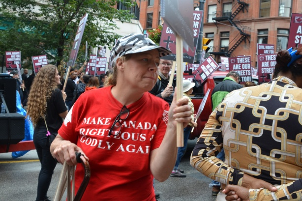 a woman wears a red T shirt that says make Canada righteous and godly again.