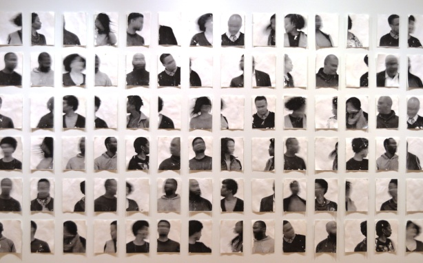a collage of many black and white blurred and uncentered portraits of people on a wall in an art gallery, part of Blur series by Sandra Brewster
