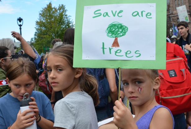 at the climate strike rally at Queens Park on a sunny morning in September, a young girl holds a homemade sign that says save are trees, two other girls are with her