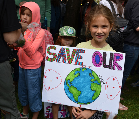 at the climate strike rally at Queens Park on a sunny morning in September, a girl holds a poster placard that she made herself, it says save our and then it has a picture of the Earth