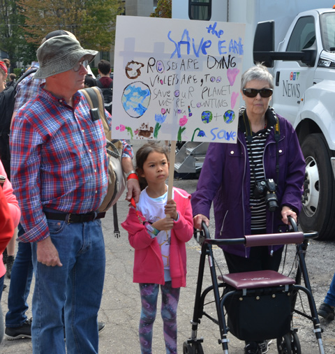 a young girl in a pink jacket stands between a woman with a walker and a man in a plaid shirt and green hat. She is holding a hand drawn protest sign