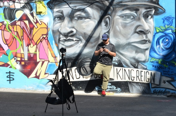 a man has set up a tripod to take a selfie of him positioned between two large faces painted in an alley