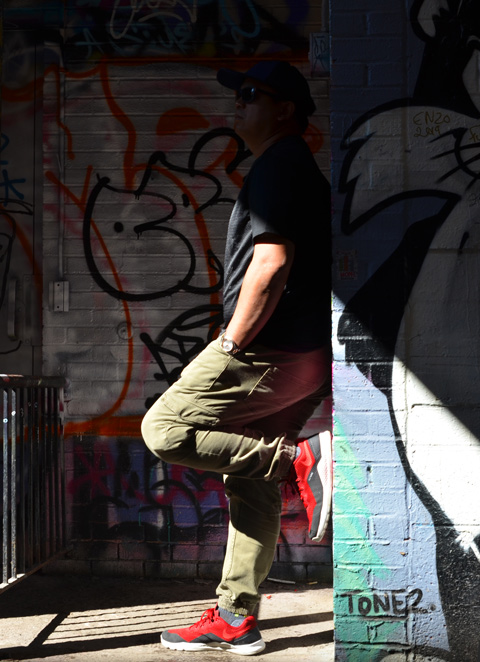 side view, man posing in a doorway in graffiti alley, top part of him is in dark shadow
