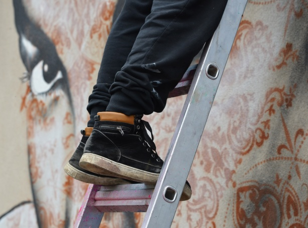 shoes on a ladder with the eye of a mural looking at them