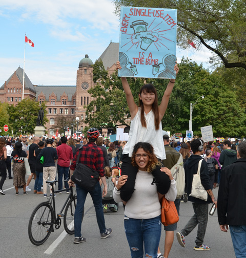 in front of Queens Park, lots of people in front, crowded out to the street, south side, on road, a woman is sitting on the shoulders of another woman while holding a sign that says each single use item is a time bomb