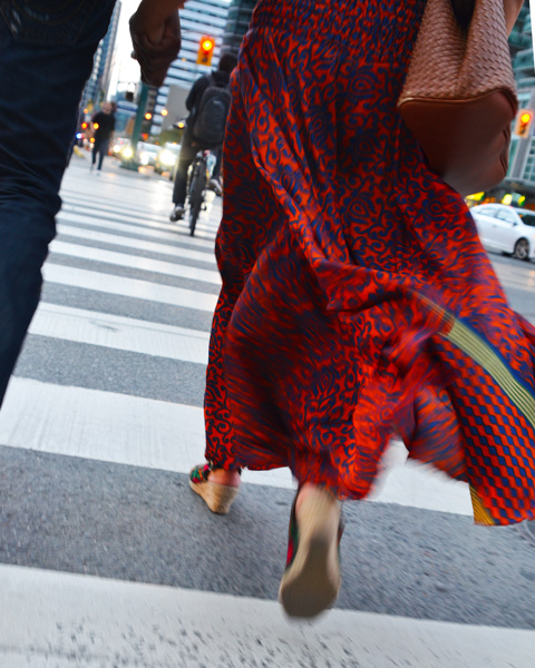 a woman's long red skirt moves as she walks across the street