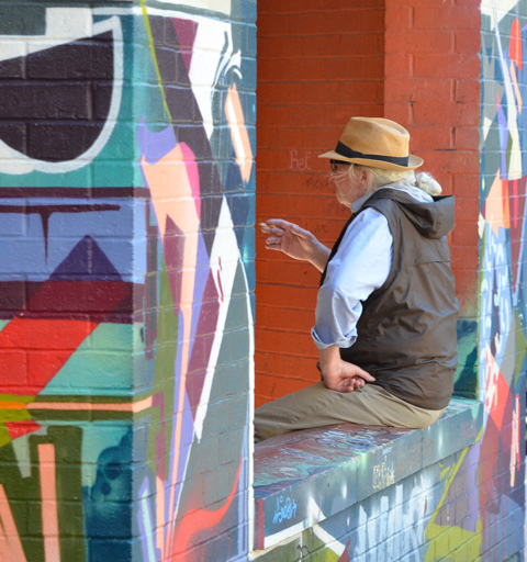 an older man in a fedora sits on a ledge covered with street art as he smokes a cigarette