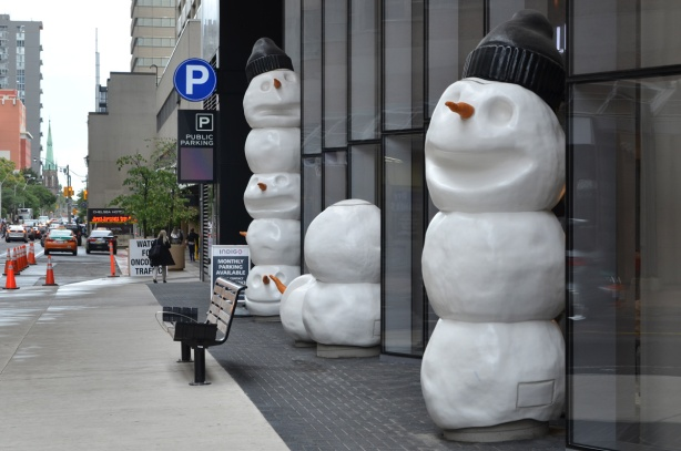 sculptures on sidewalk, snowmen, beside a new condo, one snowman has lost its head