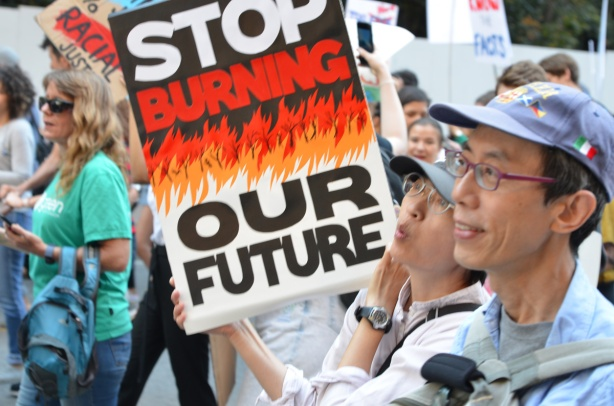 Asian couple with sign that says stop burning our future