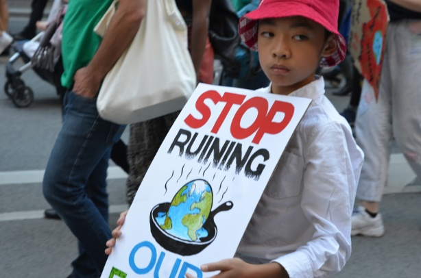 young boy with sign that says Stop ruining our planet