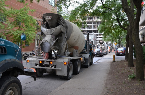 five or six cement trucks parked on a side street