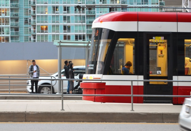 back end of a new TTC streetcar, at a stop on Spadina, people waiting, a man is on his phone as he waits, condo behind