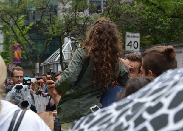 someone is talking a selfie with a girl in a green jacket who is being held up by her father, a pro photographer is also taking their picture