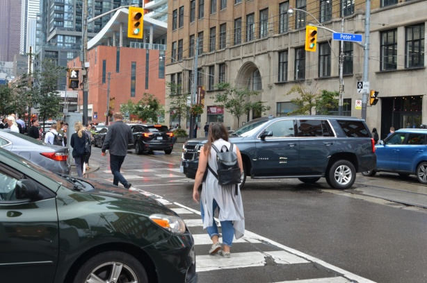 a woman crosses the street on a green light, traffic is jammed because a car has got stuck in the intersection on a red light