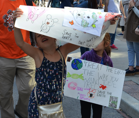 people at Toronto climate strike, walking along Wellesley street with signs, young girl holding a bristol board home made sign that bends backwards as she walks so it's hard to read it. younger girl beside her has a sign that says Treat the earth