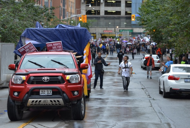 David Lynn and another man help to back up a red pick up truck with a trailer holding a stage as they reverse down Church Street during a protest march in downtown Toronto