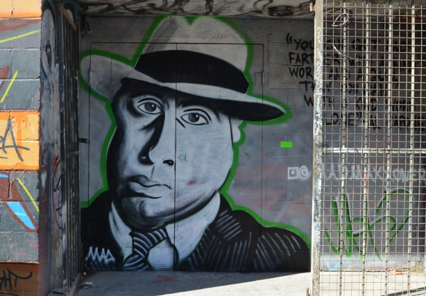 mural in an alley doorway, portrait of Al Capone in shades of grey, wearing a fedora, accompanied by words