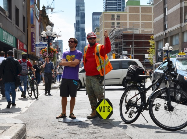 two men standing beside a police bike on the street. on the right, a construction workman with orange reflective vvest, holding a slow sign upside down and on the left, a young man in a purple t shirt and dark shorts, watching a protest on Yonge street