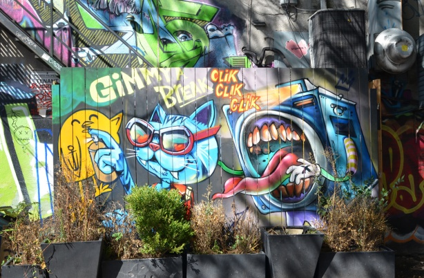 street art by uber5000, a yellow birdie, a blue cat and a characterization of a camera as a face with large mouth and sharp teeth, also with long tongue sticking out. words say gimme a break clik clik clik