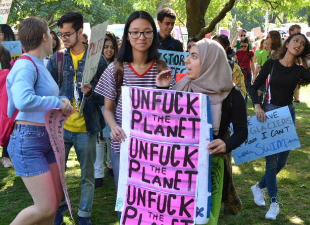 unfuck the planet, three times on pink paper, protest sign