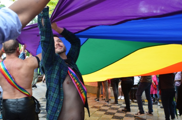 two men help to spread a giant size pride rainbow flag at Barbara Hall park
