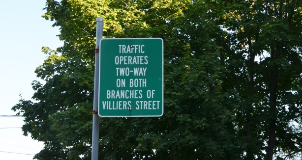 green road sign that says Traffic operates two way on both branches of Villiers street