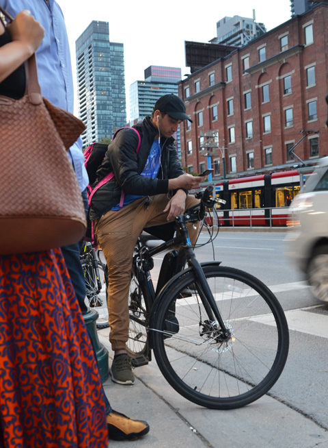 a young man sits on his bike and checks his phone while waiting at an intersection for the traffic lights to change