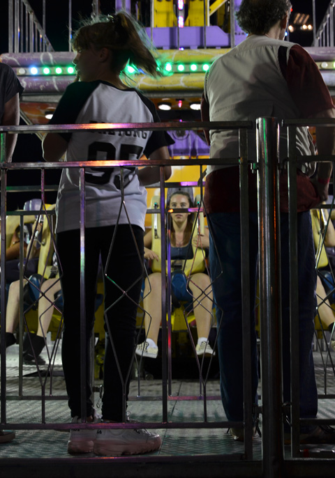 two people standing in line waiting their turn for a ride at the ex while others are already seated