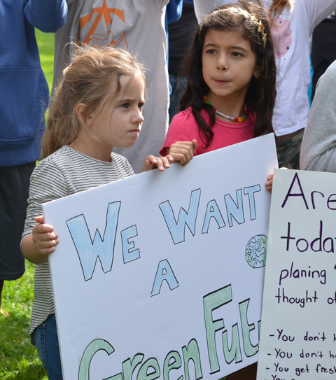 two little girls holding a bristol board protest sign that says we want a green future