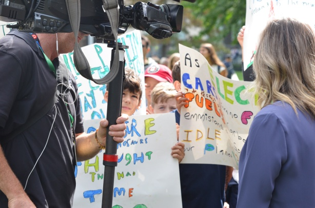 at the climate strike rally at Queens Park on a sunny morning in September, a group of school kids holding protest signs that they've made, but keeping their eyes on a man with a large TV camera
