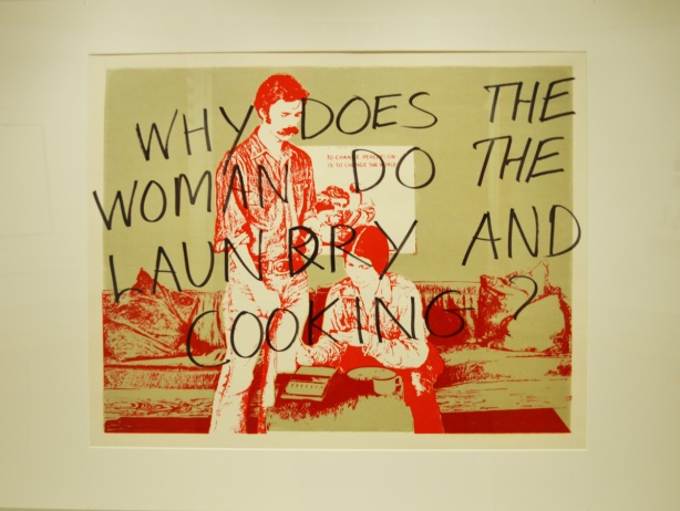 q print that shows a woman working, in red ink on green background, with black words written on top of it, why does the woman do the laundry and cooking
