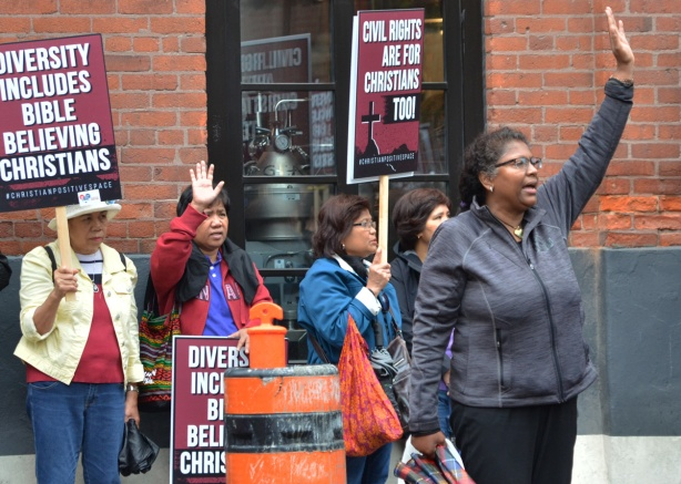 a group of wimen lined up against a wall, on the street, with hands in the air, some have signs that say Civil rights are for Christians too